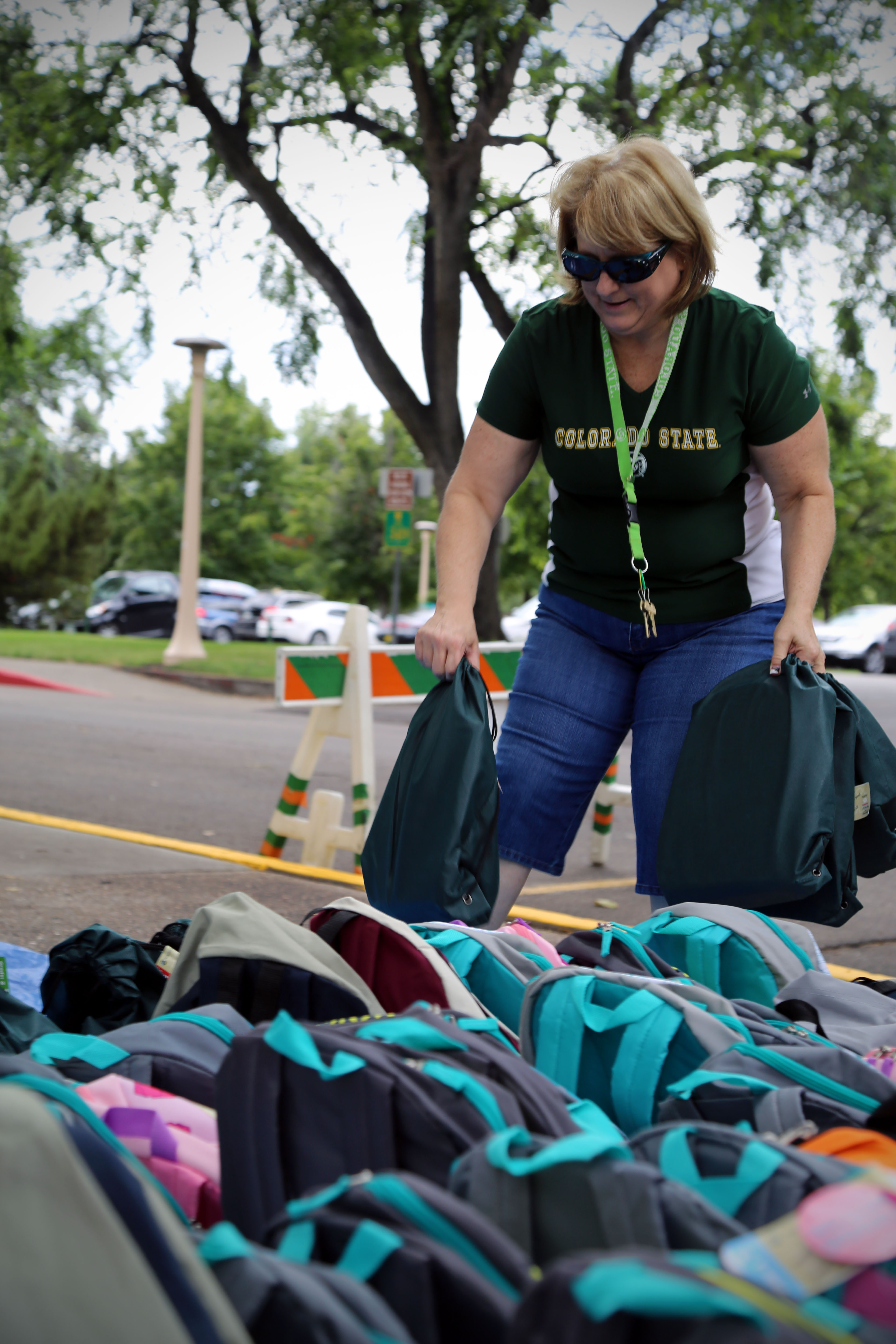 A volunteer loads backpacks for School is Cool drive.