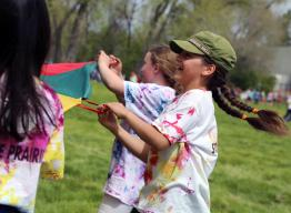 Students playing outside with a parachute.