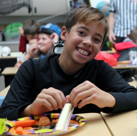 A student enjoys a plateful of treats at a Halloween party.