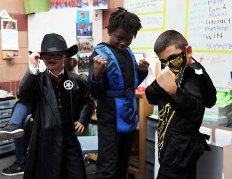 Three boys dressed in black costumes show their strength.