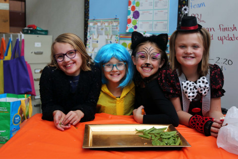 Four Olander students in costume smile at the camera