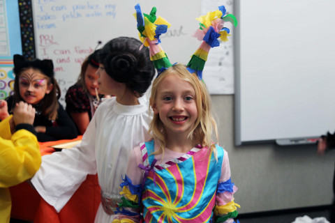 A young girls with colorful horns on her head.
