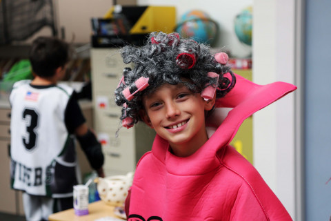 A boy with curlers in his hair at a Halloween party.