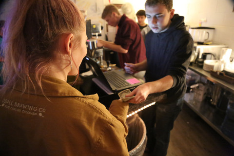 A cashier helps a customer at Cup of Joe cafe.