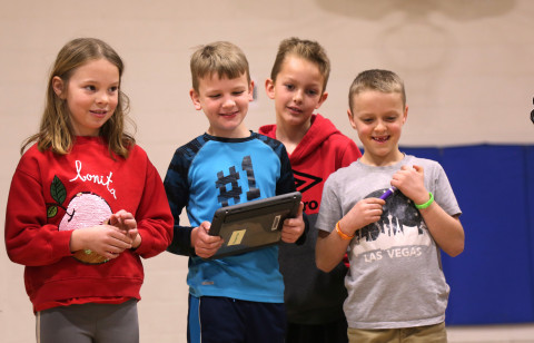 Four elementary students smile while watching their robot.