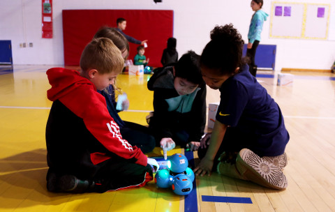 Elementary students code a small robot made of three blue balls.