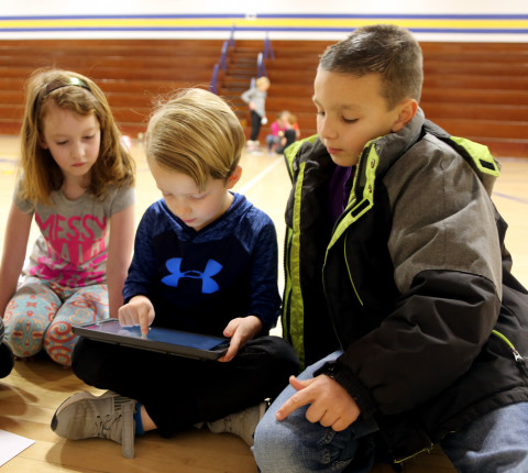 Elementary students work on an ipad coding a robot.