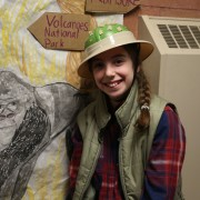 A fifth grade girl dressed up as Diann Fossey in front of a gorilla poster she made.