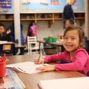 A first-grade girl at Putnam works at her desk and smiles.