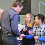 Dunn students presented miniature flags to new citizens.