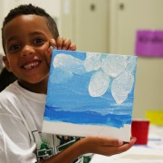 A boy proudly holds up his scenic painting.