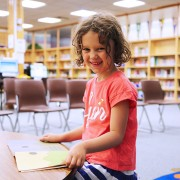 A smiling girl sits in the library with a book