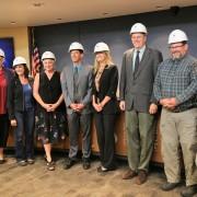 Board of Education members pose wearing hard hats.