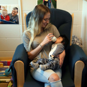 A teen parent feeds her baby at the childcare center at school.
