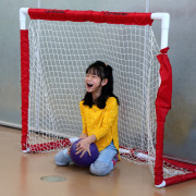 A young elementary student smiles big while in the soccer goal.