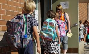 Elementary kids walking into a school.